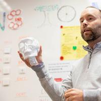 Man holding a white 3D printed skull