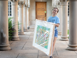 student walking with a framed work of art wrapped in plastic covering.