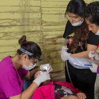 students examining someones teeth
