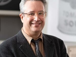 Man with short gray hair and glasses posing in dark brown suit.