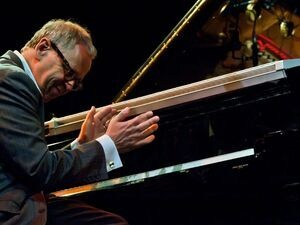 Kenny Werner at the piano, smiling and clapping hands.