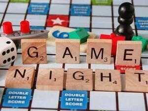 scrabble board game with letters that spell game night.