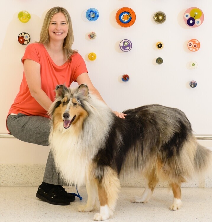 Dr. Leigh Anne Clark sitting with dog (standing)