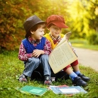Children reading a book outside