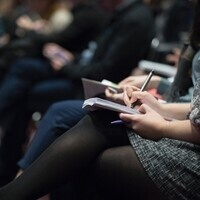 A person takes notes during a meeting