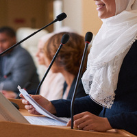 Photo of a female at a podium speaking.