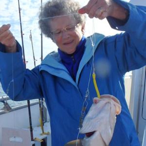 Karin Limburg holds fish on fishing line