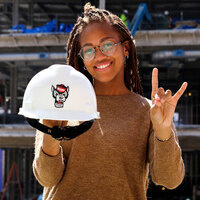 A student holds a hard hat.